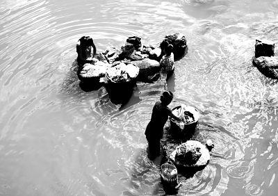 Dones rentant a riu contaminat a Guatemala.